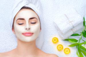 client relaxing with a face mask on with three candles, three small towels and a plant stem next to her