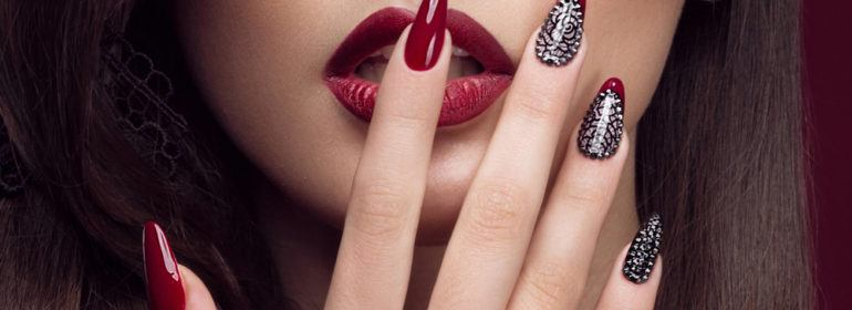 brunette model with red stiletto nails placing index finger over open red lips