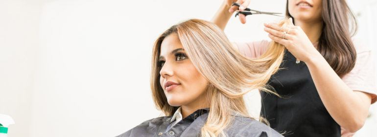 brunette hairstylist cutting blonde female's medium-length hair