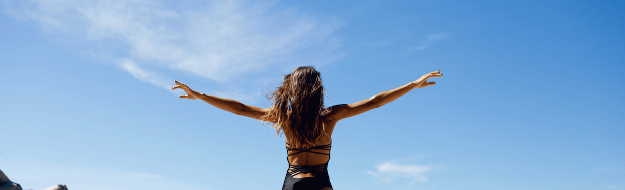Woman with arms outstretched at the beach