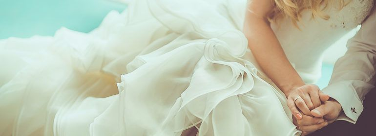 bride in ruffled skirt cuddles with her groom
