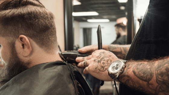 tattooed barber cutting a man's hair with clippers