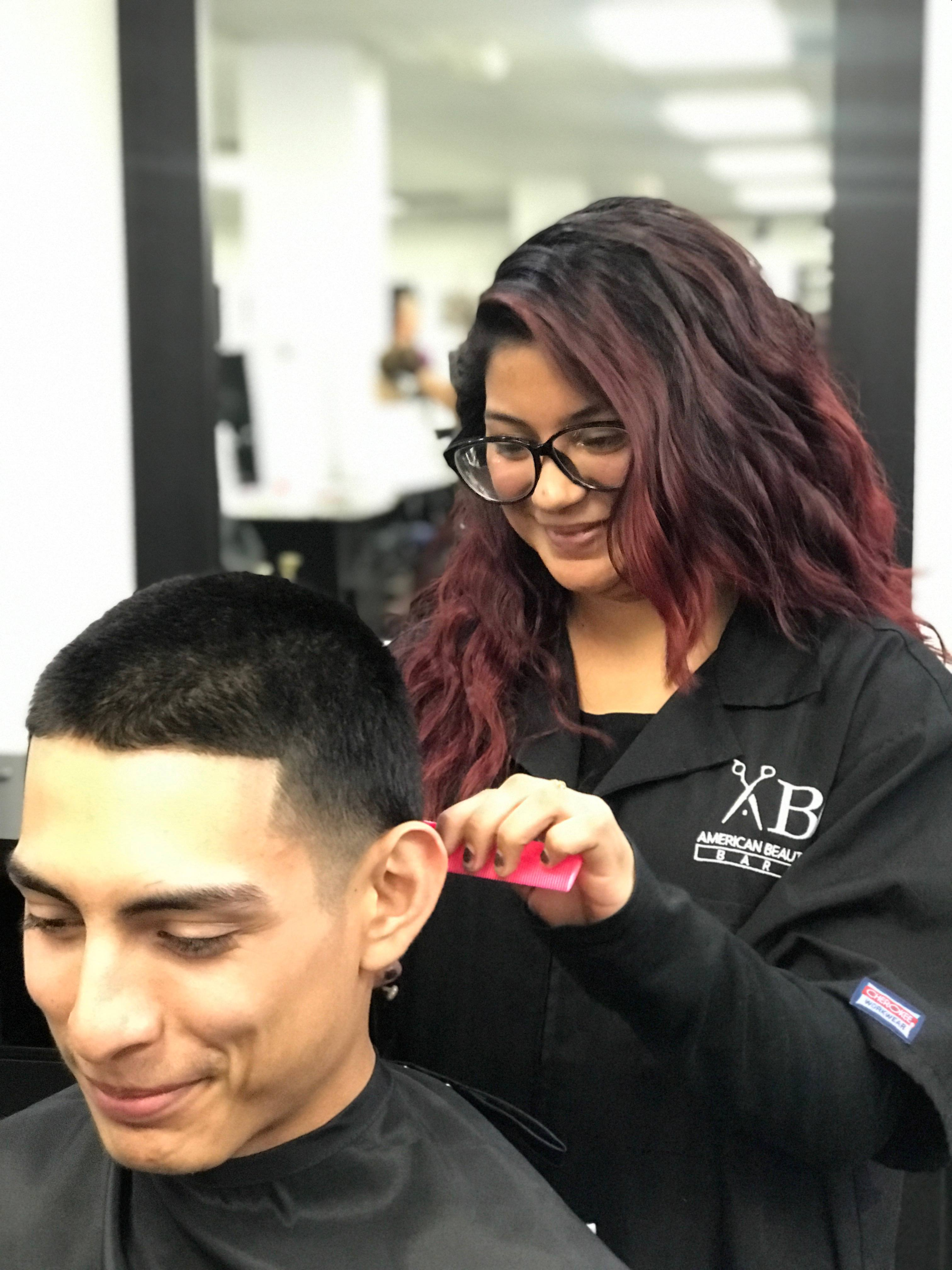 Mayra Zuniga, barbering student working on a client.