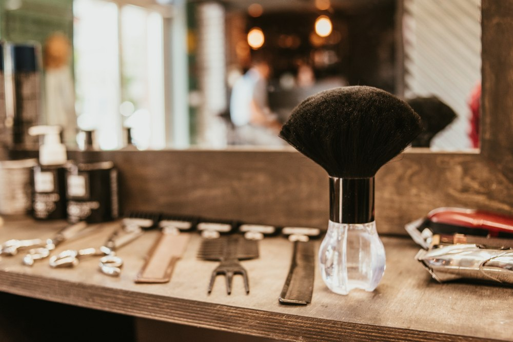 barbering tools lined up on station in front of mirror