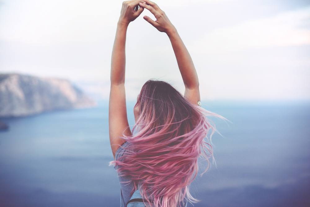 girl with pink hair holding hands in the air over the ocean